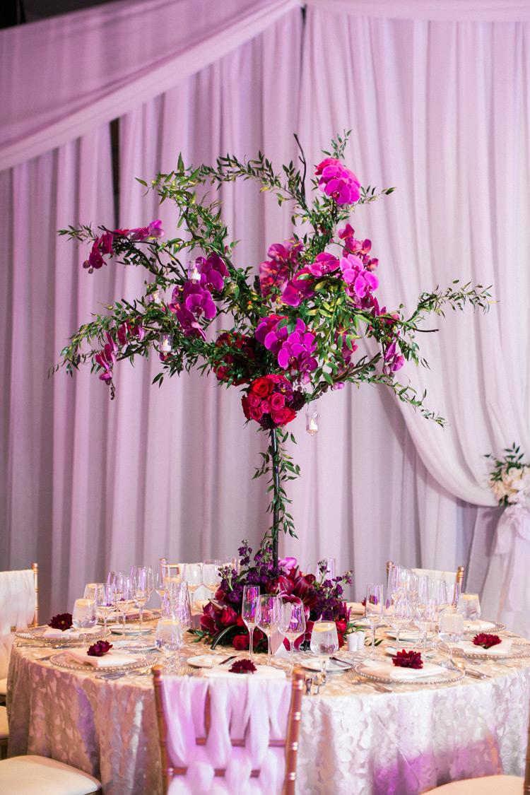 Romantic, deep colored flower arrangement on table.