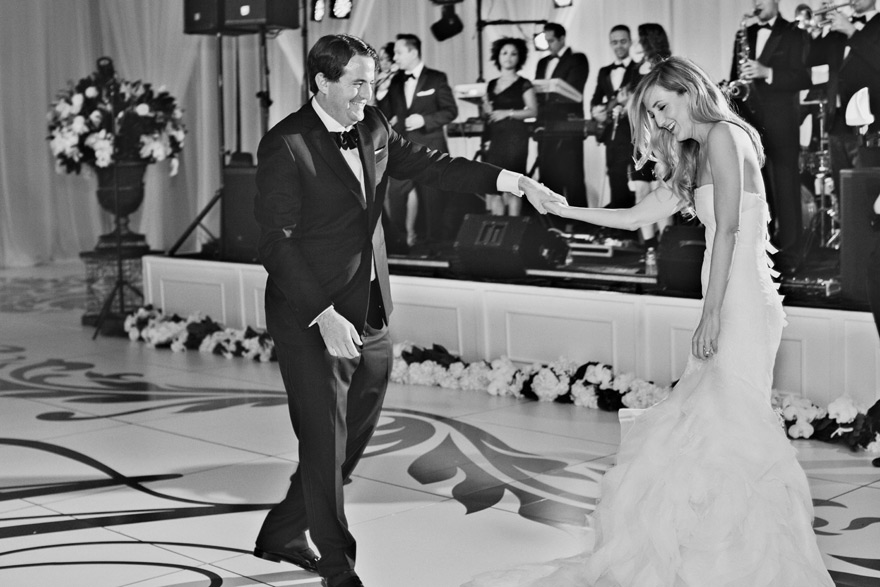 Bride and groom smile during first dance moves. Live band sings and plays instruments.