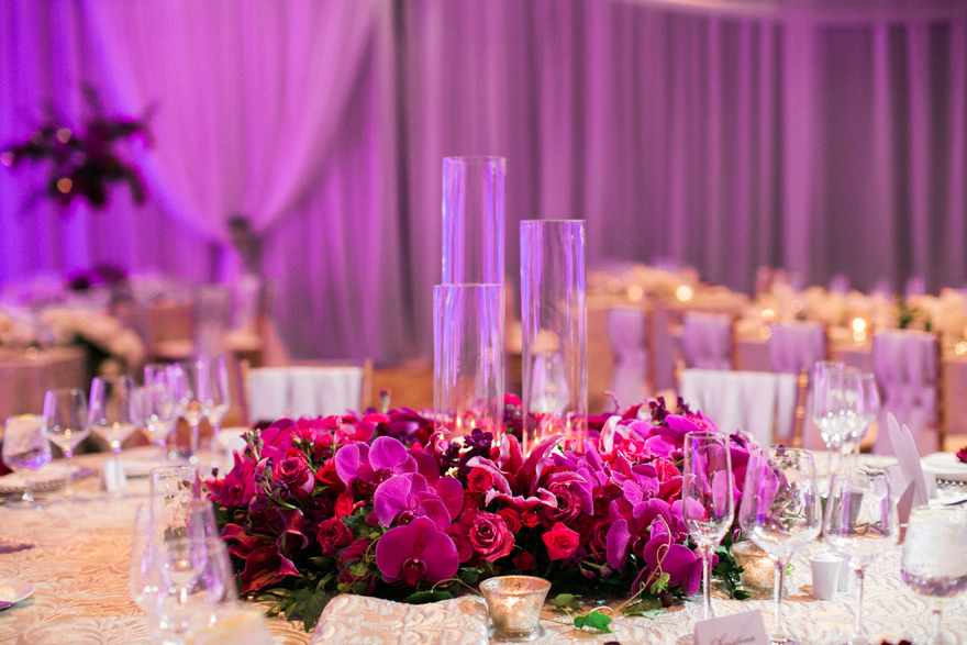 Glass settings and fuchsia arrangement centered on table placement.