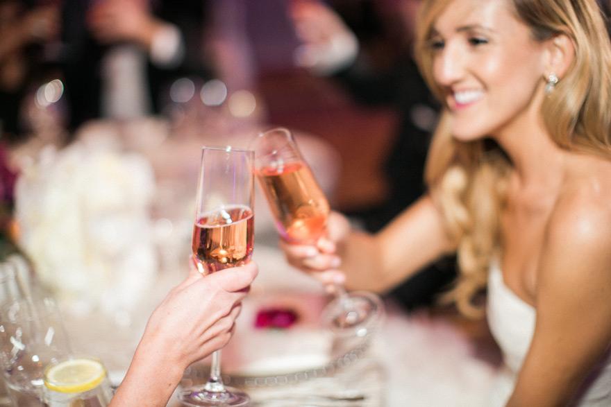 Bride and bridesmaid cheer during wedding reception. Scottsdale weddings.