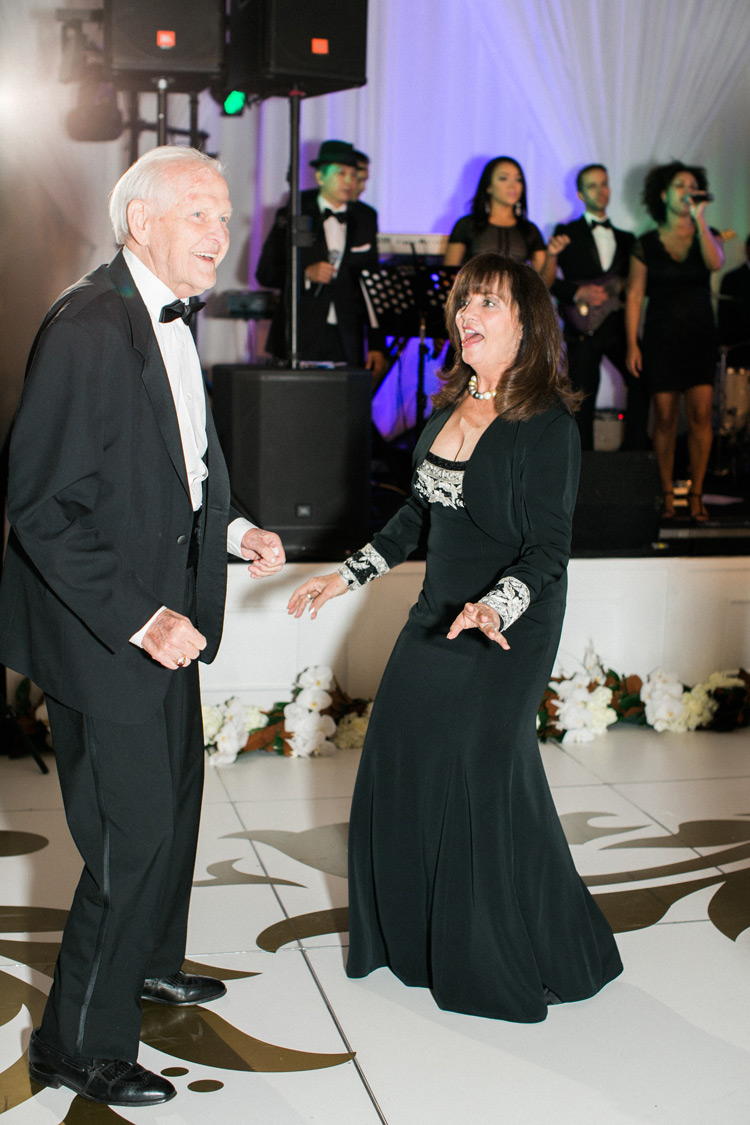Older couple dances during wedding reception on elegant dance floor.