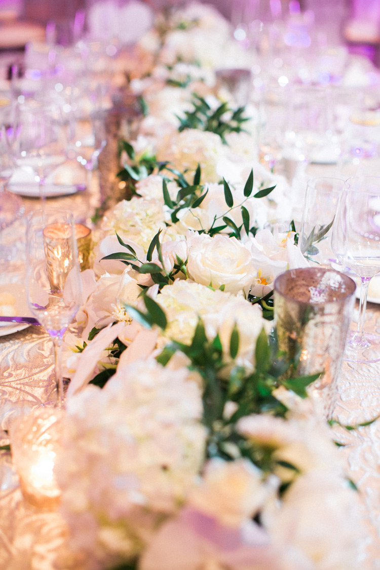 White flower arrangement and gold placements on bridal party's table.