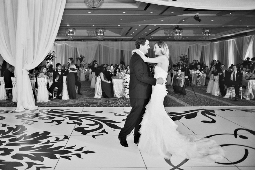 Groom holds bride while having their first dance. Guests watch this sweet moment.