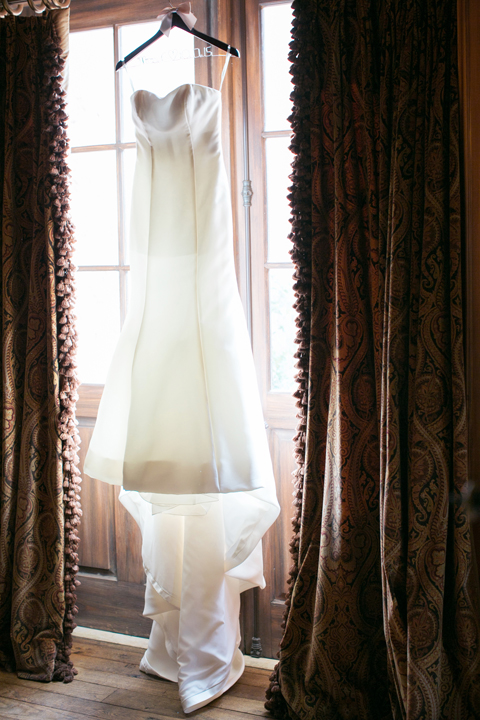 Strapless fit-and-fare wedding gown hangs in the window