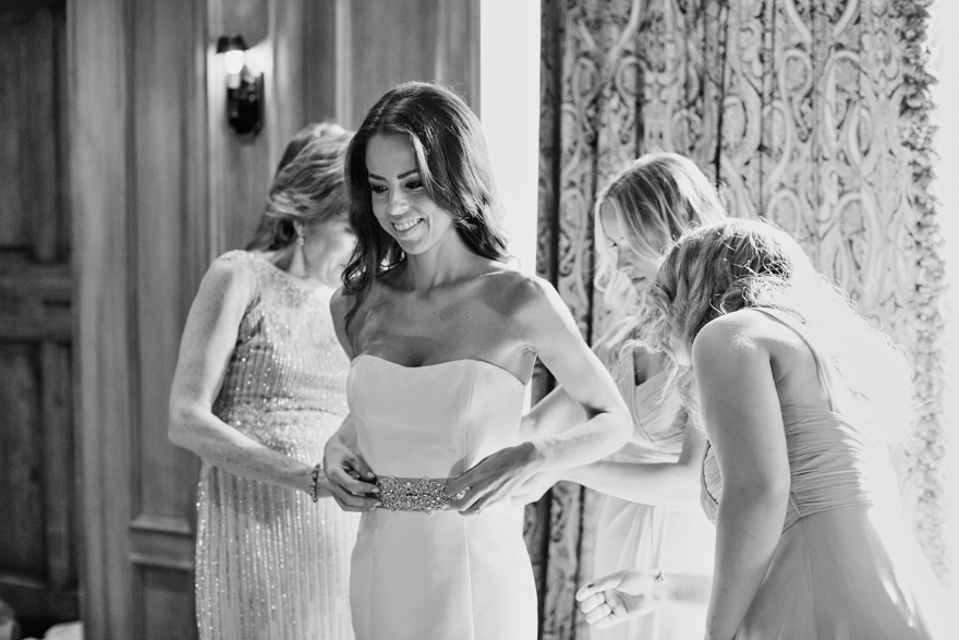 Smiling bride is helped into her gown by her mother and friends