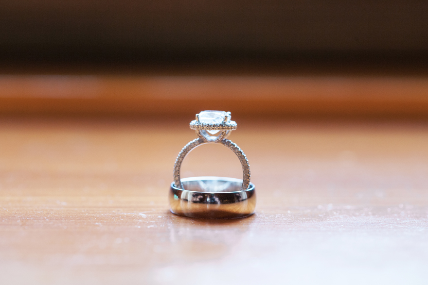 Engagement ring with a halo setting and open gallery sits upright in the groom's wedding band.