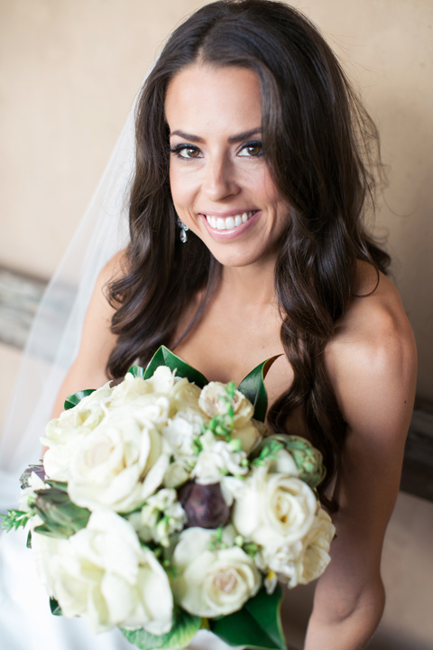 Happy bride with loos, dark hair. Bouquet with white roses, artichoke, magnolia leaves.
