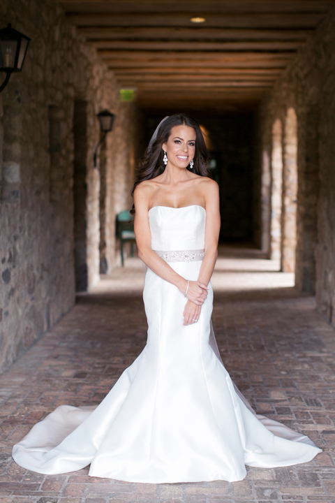 Full length bridal portrait of a bride with loose hair and a strapless fit-and-flare gown