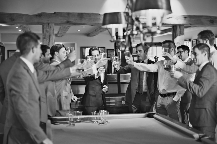 A room full of groomsmen toasting the groom on his wedding day