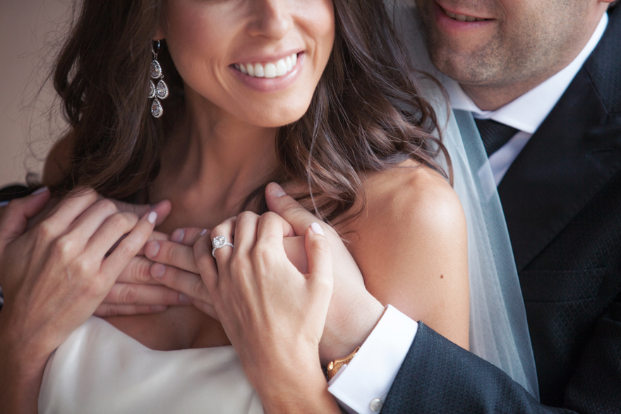Close-up portrait of the groom embracing his bride from behind. Focus on the engagement ring