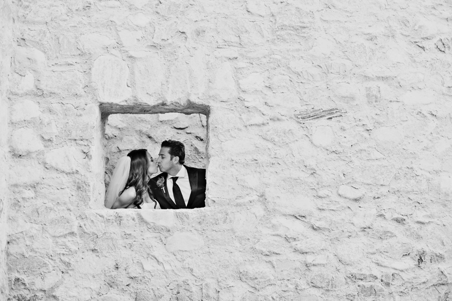 Bride and groom seen through the window in a stone wall. Silverleaf