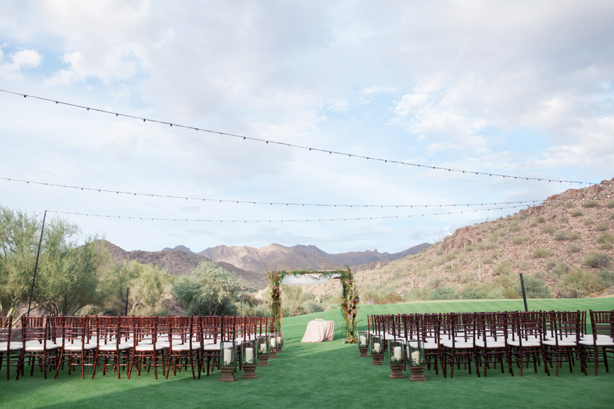 Outdoor wedding ceremony with a draped chuppa and wooden chairs. Arizona wedding