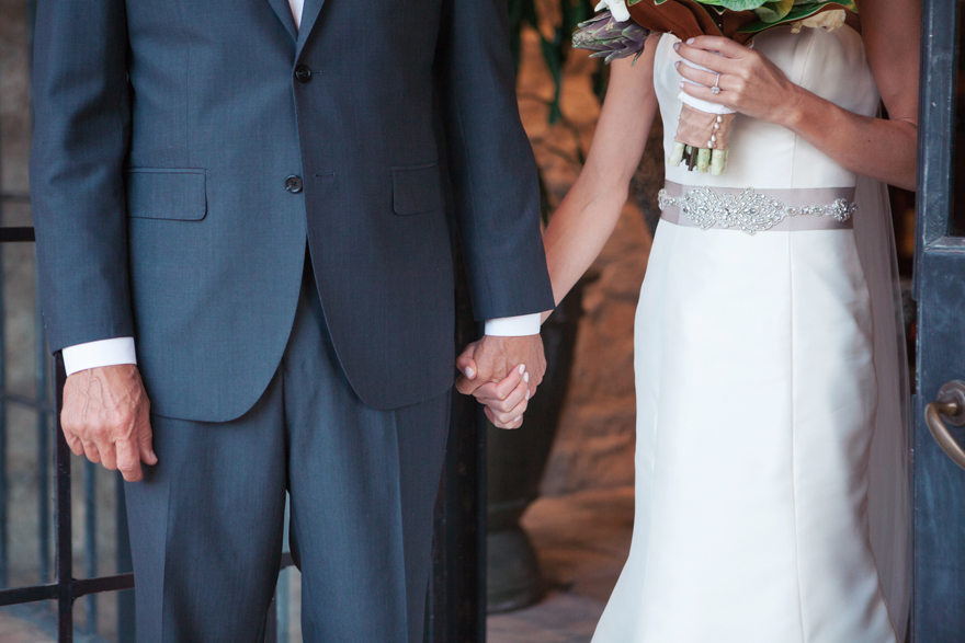 Bride clasps her father's hand before he escorts her down the aisle.