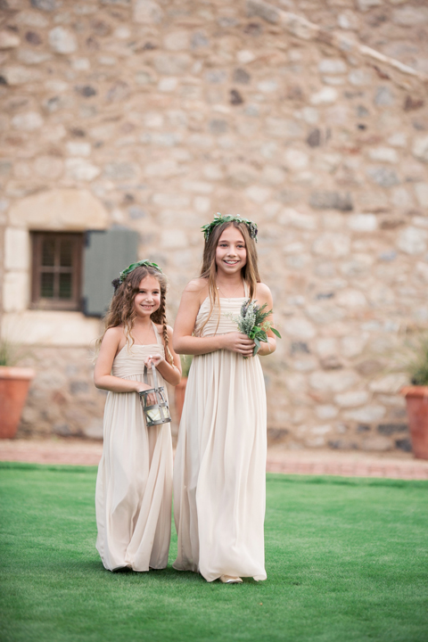 Flower girls in pale dresses with wreaths on their heads. Outdoor wedding ceremony