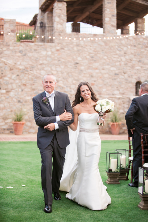 Father of the bride walks his glowing daughter down the aisle. Outdoor wedding ceremony