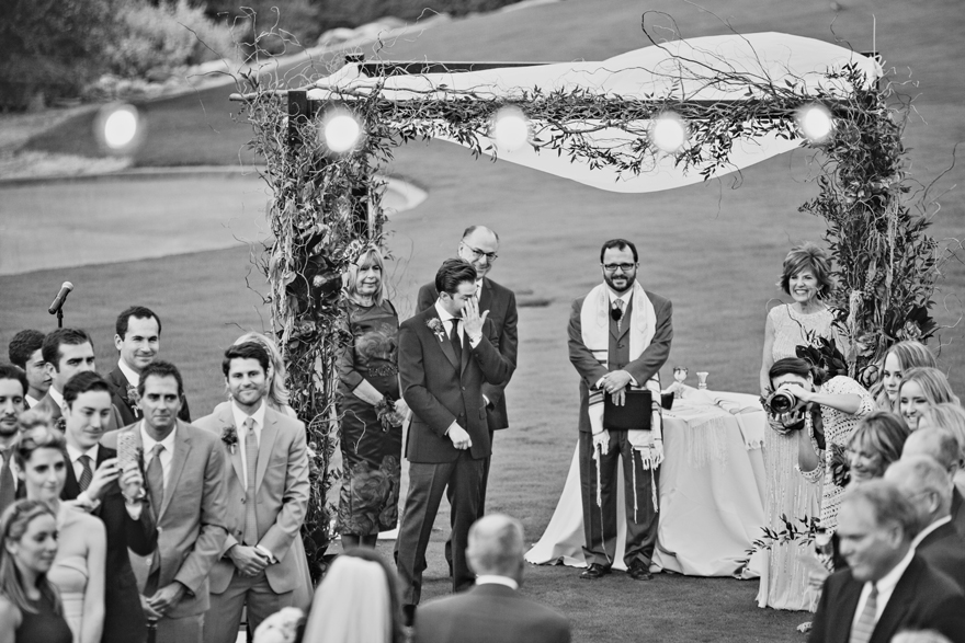 Groom cries as he sees his bride walking down the aisle. Outdoor wedding