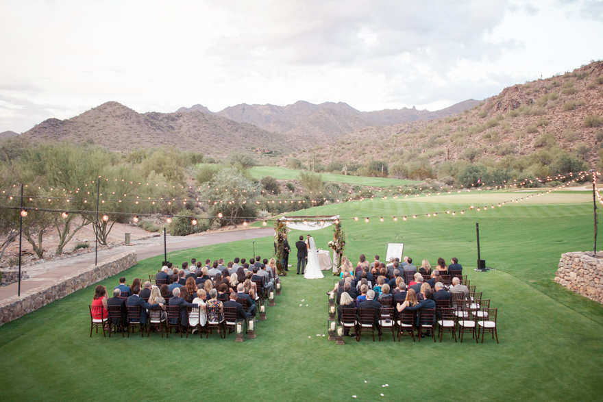 Wide shot of an outdoor wedding ceremony with the Arizona mountains and desert in the background
