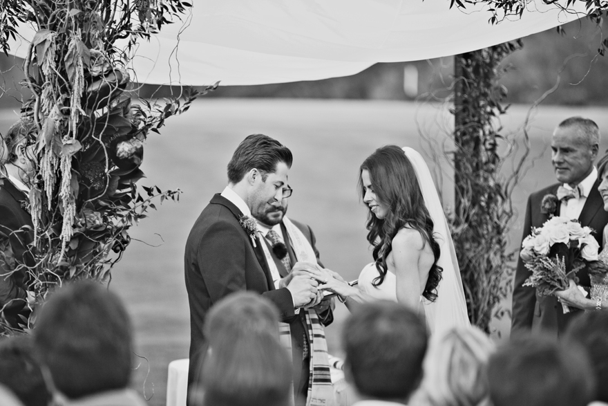 Groom slips a ring onto his bride's finger. Black and white photo of an outdoor wedding ceremony