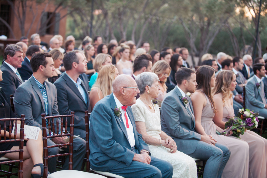 Wedding guests watch as the bride & groom exchange vows. Outdoor wedding ceremony