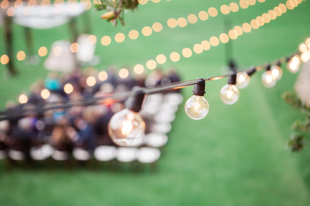 Globe lights strung above an outdoor wedding ceremony