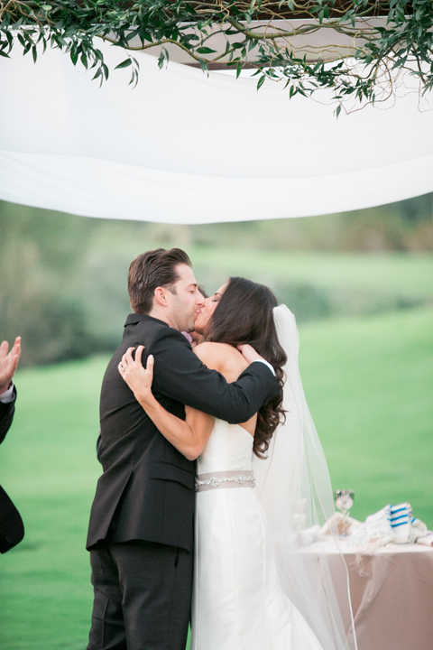 First kiss as man and wife. Outdoor wedding ceremony