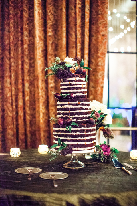 Three tier naked cake. Chocolate wedding cake decorated with flowers and figs.