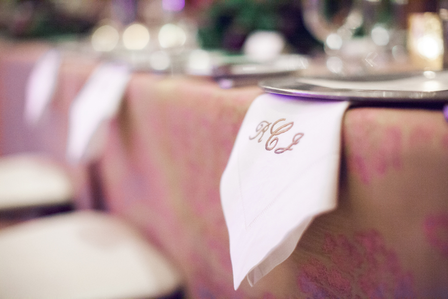 Brocade tablecloth and monogrammed napkins at an elegant wedding reception