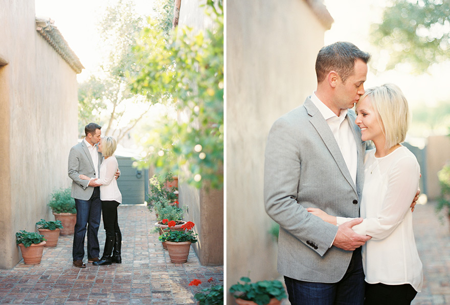 Groom gently kisses and holds bride near house setting