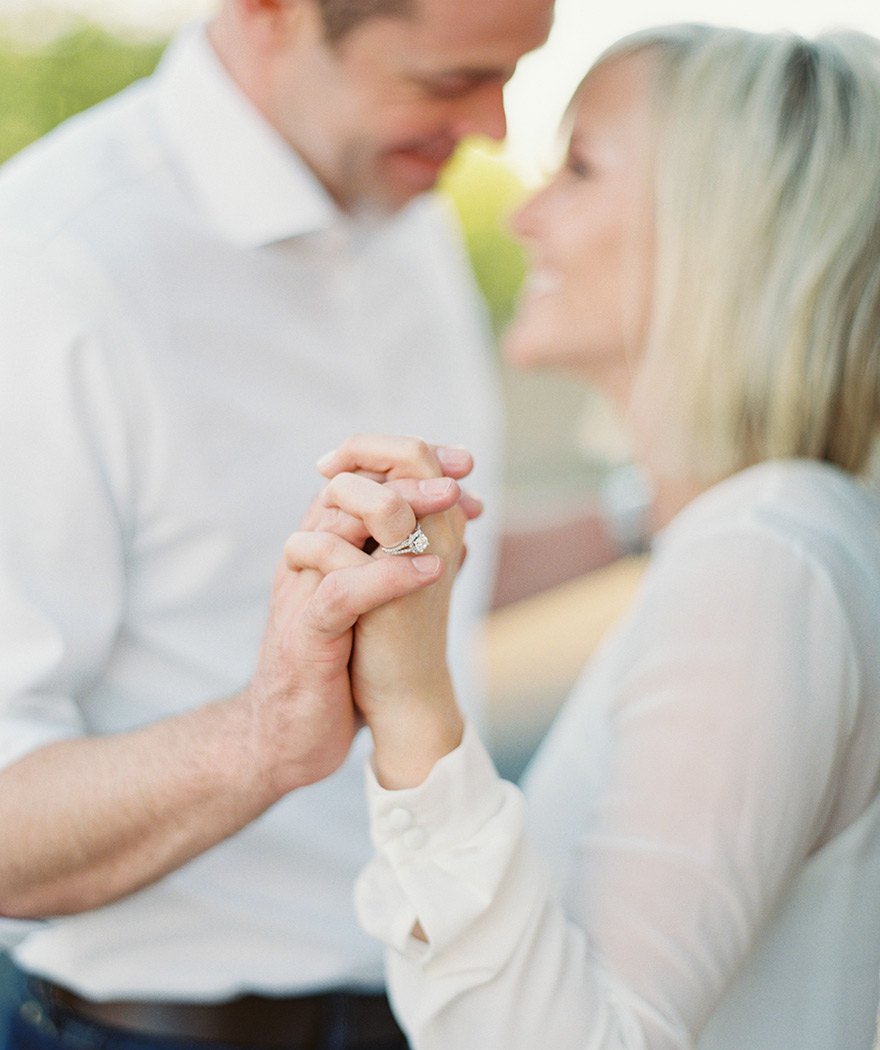 Couple share special moment holding hands portraying brides ring as they face one another