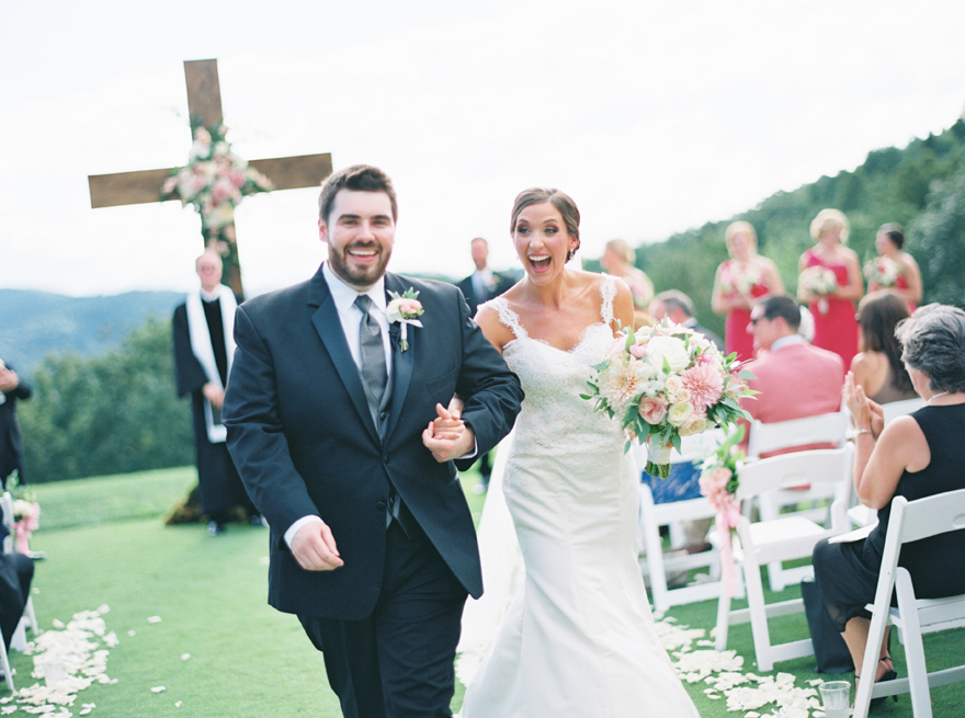 Laughing newlyweds walk back down the aisle