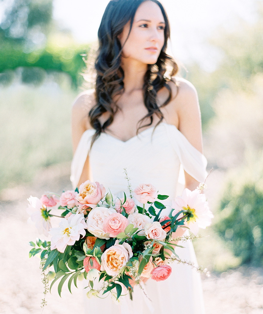 Lush bouquet of pale corals and pinks with an off-shoulder dress