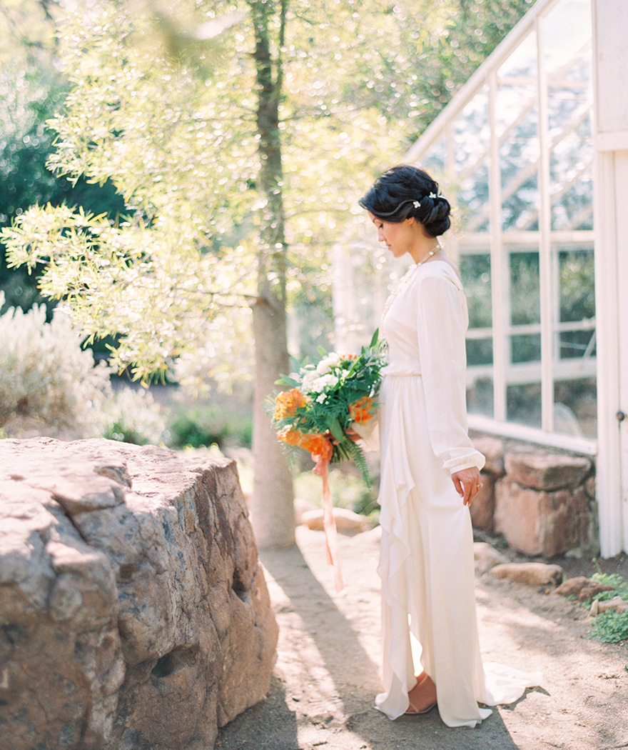 bride in a long-sleeved dress with orange flowers