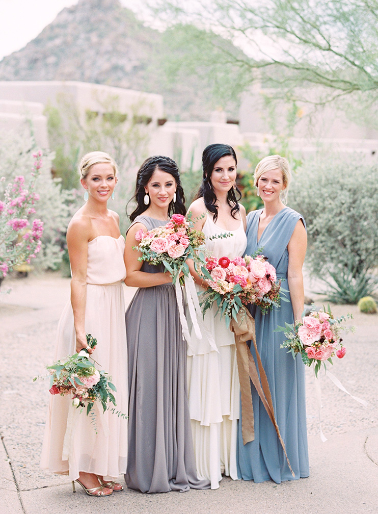 bridesmaids in draped gowns with pink flowers