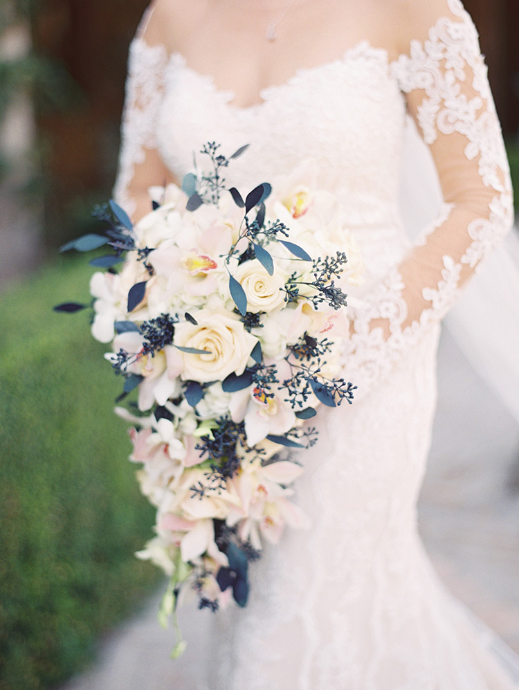 cascade bouquet of roses and orchids with navy blue accents