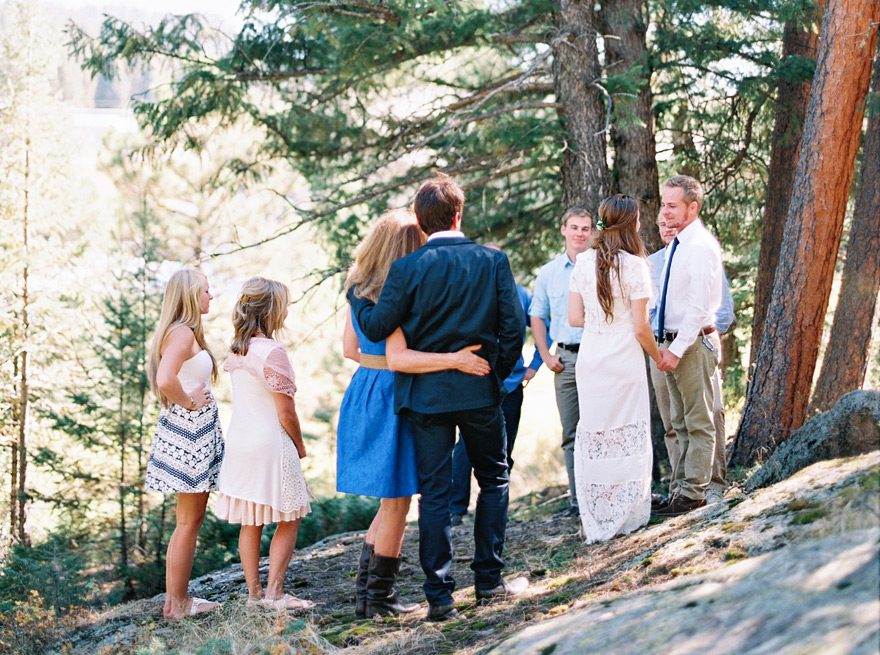 Couple joins hands while family watches them join in unity of marriage. Outdoor casual wedding.