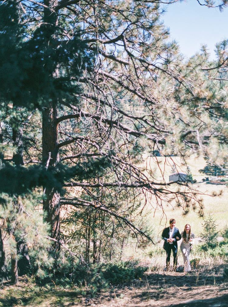 Bride walking through green forest with father. Colorado pine tree outdoor wedding.