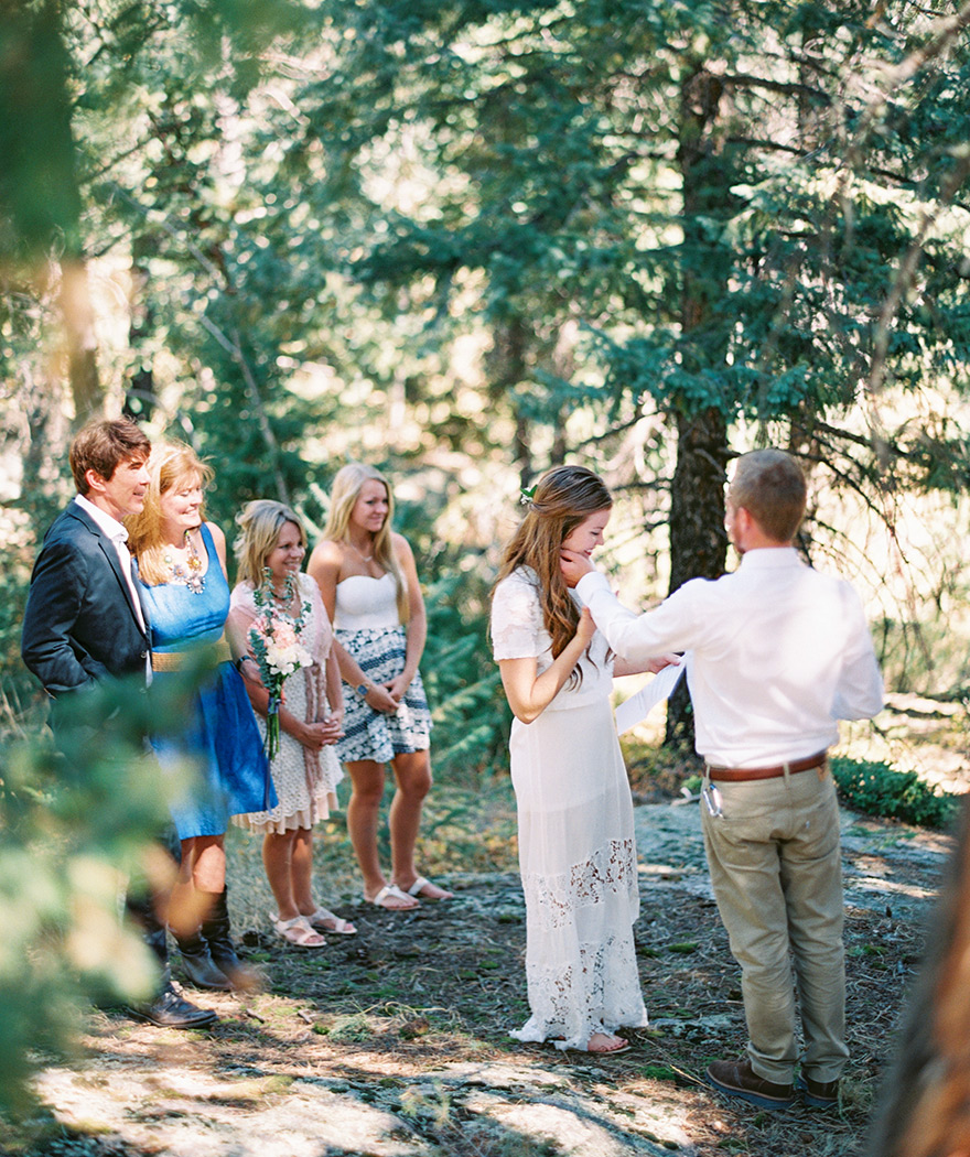 Bride reads vows while groom embraces moment. Casual boho wedding outdoors