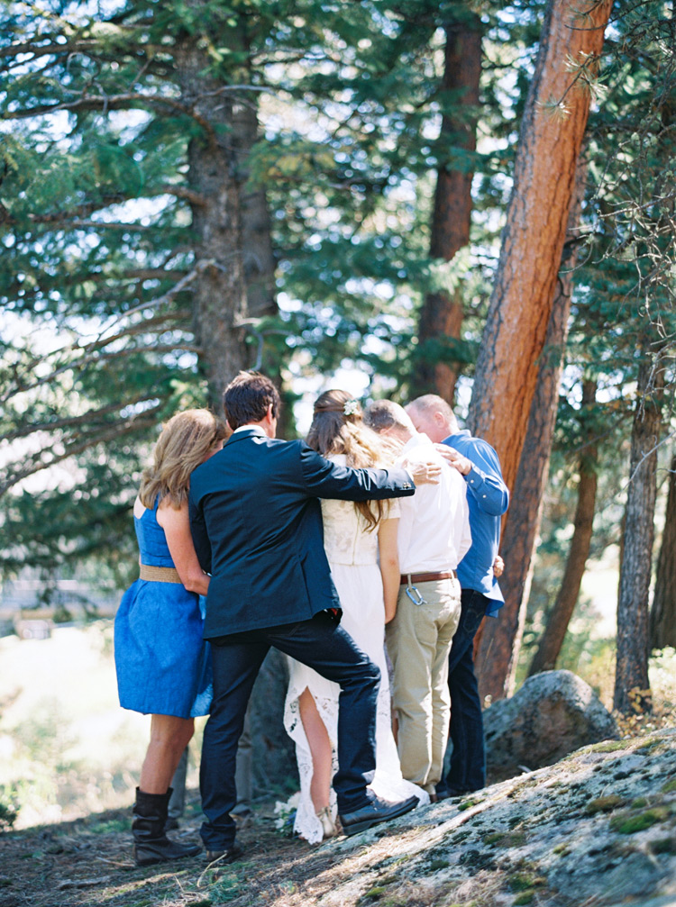 Family surrounds couple in outdoor pine trees moment