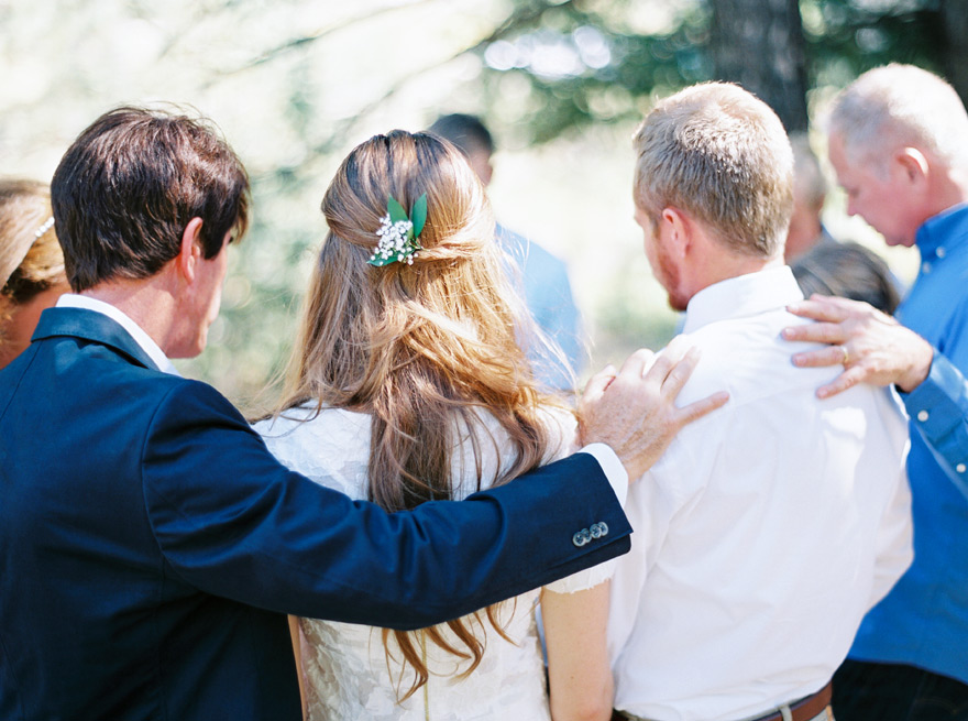 Family surrounds couple outdoors and takes a moment to pray. Simple wedding shoot