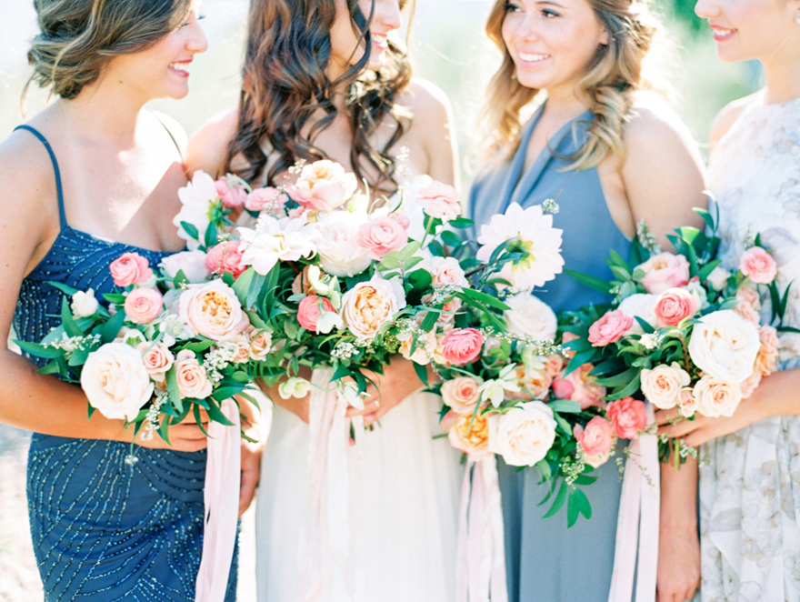 Bridesmaids in shades of gray, holding pink and coral bouquets, smile with the bride