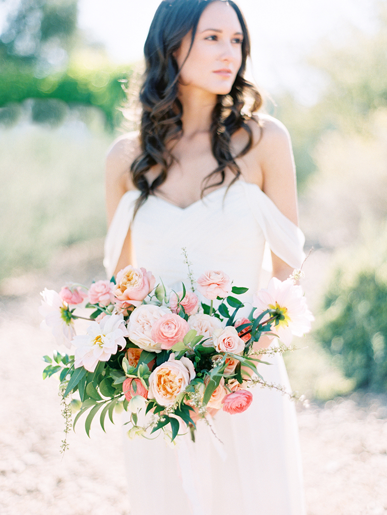 Delicate bride in a dress with off-the-shoulder draping. Hair in long, loose waves. Pink bouquet