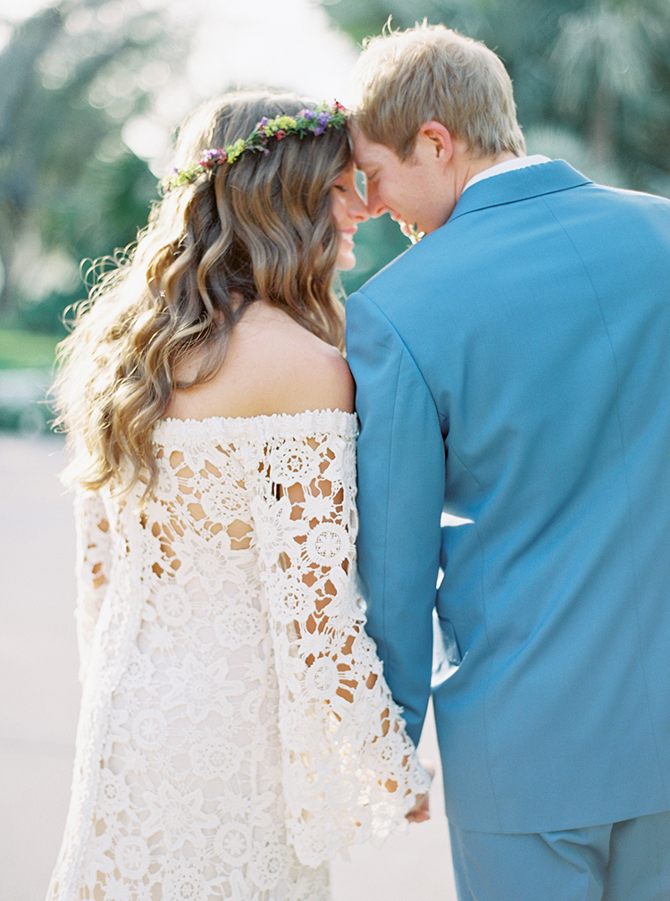 Bohemian dress and delicate flower crown for the bride. Blue suit for the groom.
