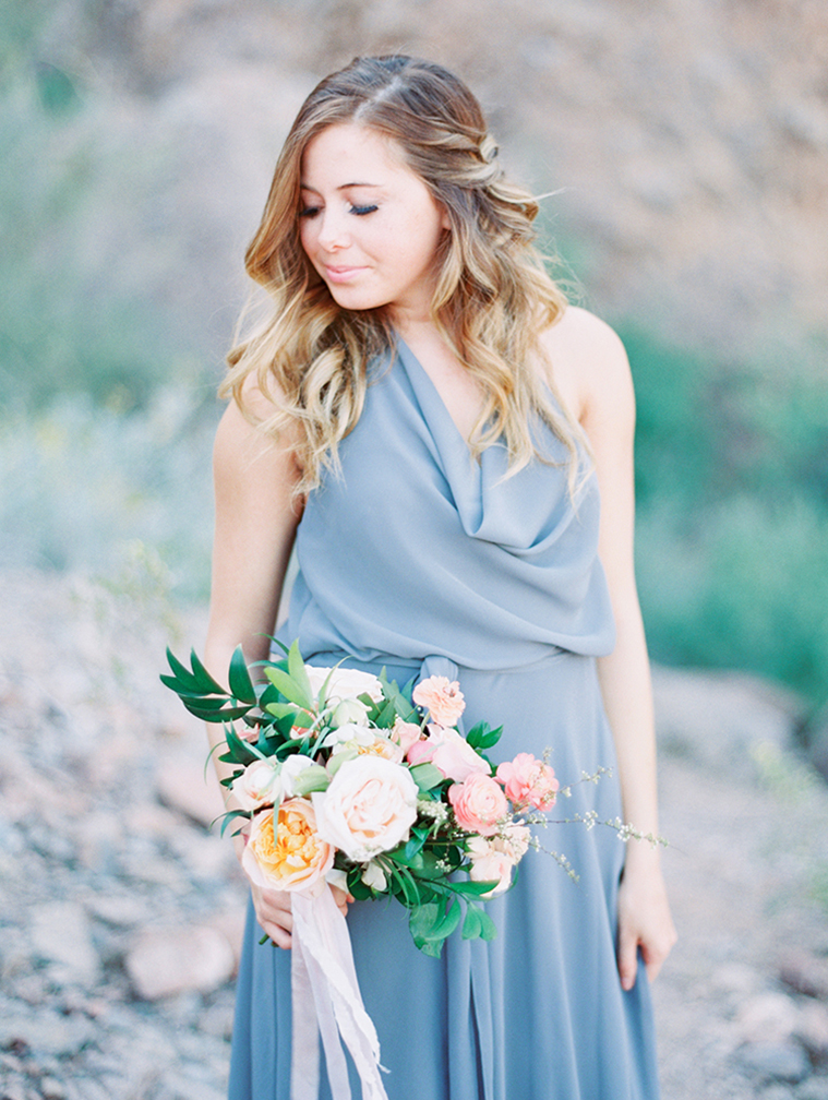 Bridesmaid in gray, draped dress with her hair in a modern, loose style. Pink flowers.