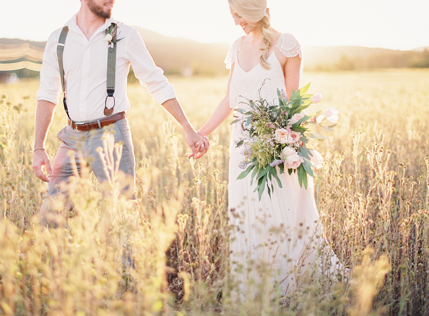 Groom in suspenders and bride in boho lace together in a golden field.