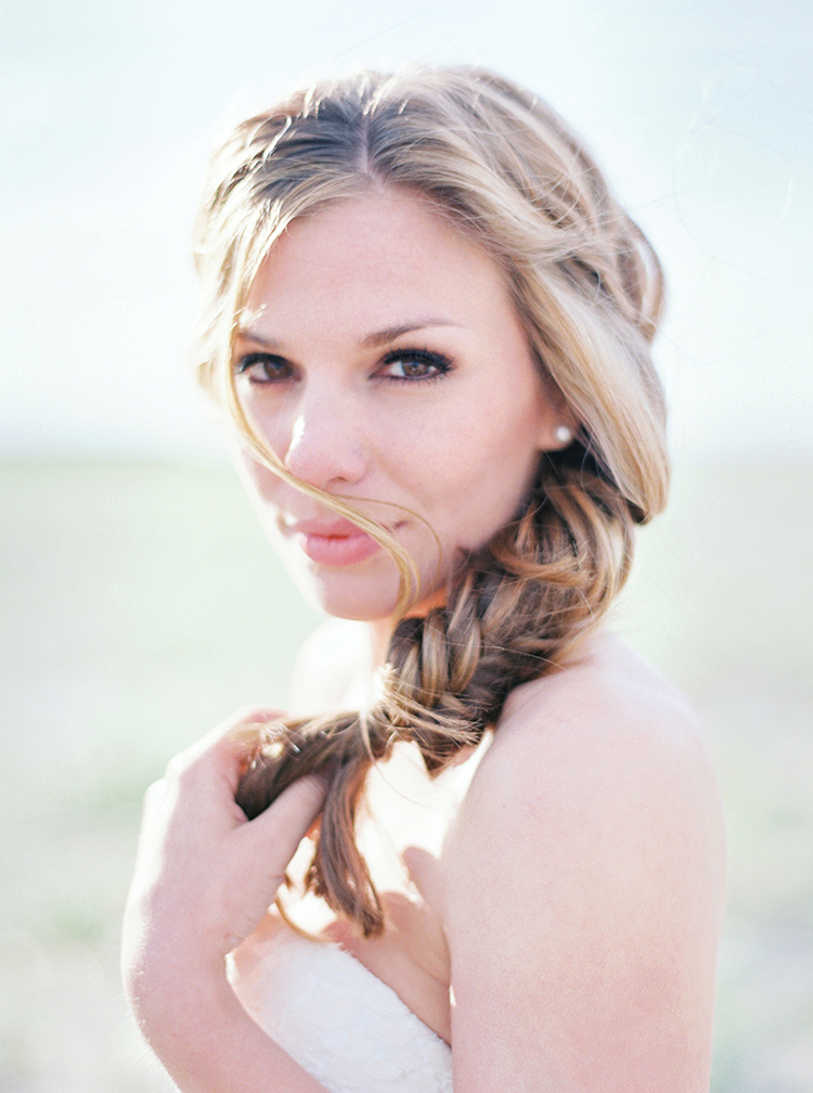 Beachy bride with her blonde hair in a fishtail braid.