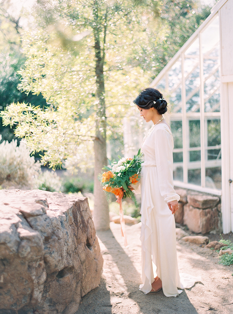 Bride in a soft, low backed gown. Orange bouquet. Dark hair in an up-do with tiny, white flowers.