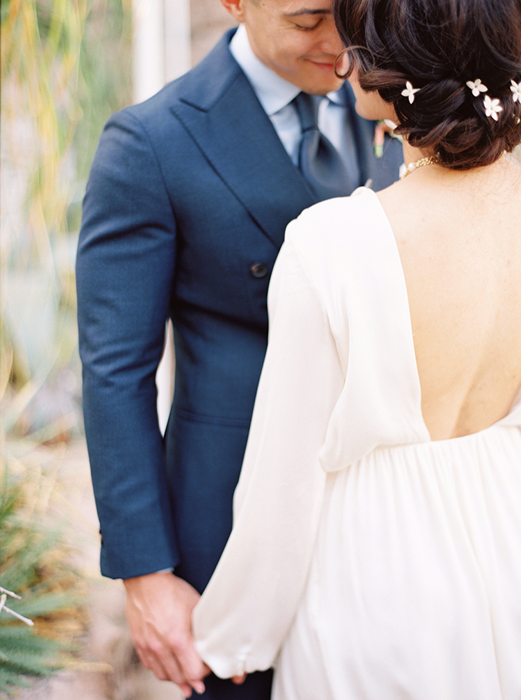 Bride in a soft, low backed gown. Dark hair in an up-do with tiny, white flowers. Groom in blue
