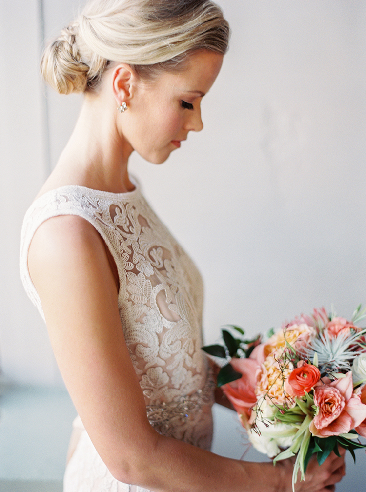 Sophisticated bridal style. Lace gown, coral flowers. Hair in an elegant up-do