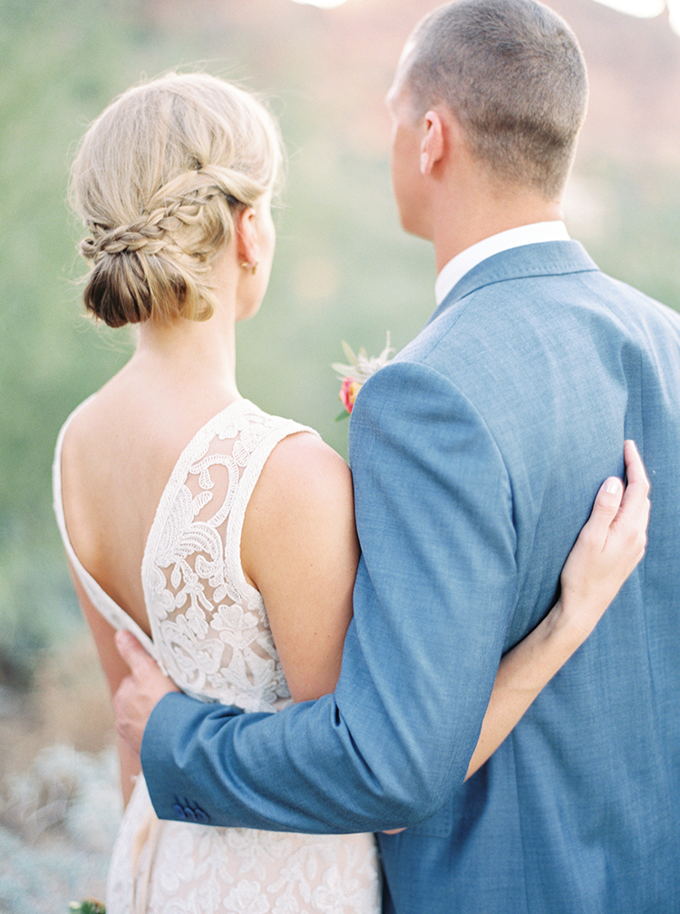 Bride with elegant up-do with braids wrapping around a low bun. Handsome groom in blue.