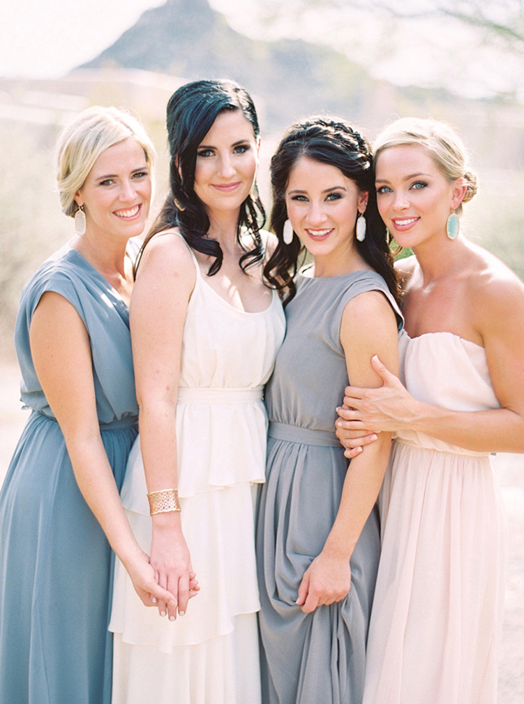 Bridesmaids in drape, neutral gowns surround the bride. Wedding style!
